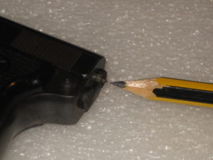 A la pointe du crayon se trouve le témoin d'armement du percuteur. On voit le cône pointu : le percuteur est armé.